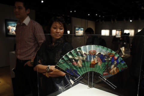 "Visitors stand in front of a hand fan during a preview of an exhibition entitled ""Gardens of Pleasure: Sex in Ancient China"" in Hong Kong"